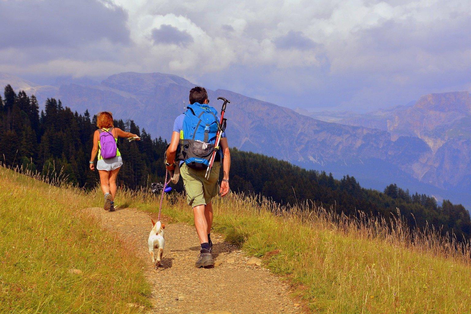 Un homme et une femme en randonnée avec leur chien, en cani-rando